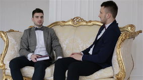 Two handsome businessmen in suits sitting on a sofa discussing business. One of the men has a planner on his lap. At the end the camera goes up stock video