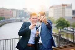 Two handsome businessmen talking a selfie Royalty Free Stock Images