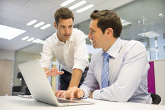 Two handsome businessmen working together on a Laptop in the off Stock Image