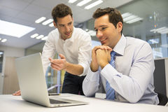Two handsome businessmen working together on a project in the of Stock Photos