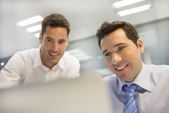 Two handsome businessmen working together on a project in the of Stock Image