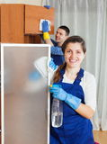 Two handsome cleaners cleaning furniture Stock Photo