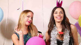 Two handsome guys hiding behind their beautiful girls in party photo booth stock video footage