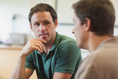 Two handsome mature students having a conversation. Sitting in class room Stock Photos