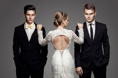 Two handsome men and beautiful bride, studio. Two handsome men and beautiful woman. Studio, trendy, strict look Stock Photos