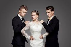 Two handsome men and beautiful bride, studio stock photos