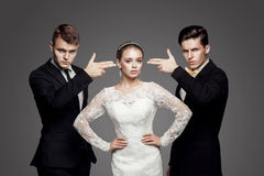 Two handsome men and beautiful bride, studio stock photography