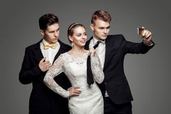 Two handsome men and beautiful bride, studio royalty free stock photography
