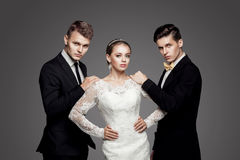Two handsome men and beautiful bride, studio stock images