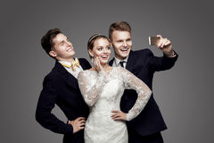 Two handsome men and beautiful bride, studio royalty free stock photos