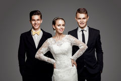 Two handsome men and beautiful bride, studio royalty free stock photo
