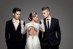 Two handsome men and beautiful bride, studio Royalty Free Stock Image