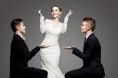 Two handsome men and beautiful bride, studio. Two handsome men and beautiful woman. Studio, trendy, strict look Royalty Free Stock Image