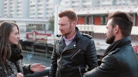 Two handsome men and a beautiful girl talk standing near a bridge railing. Girl is surprised, then smiles. Slow mo. Two handsome men with beards and a beautiful stock video