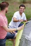 Two handsome men camping in woods stock photos