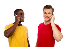 Two handsome men communicating on cellphone. African guy looking at caucasian male Stock Image
