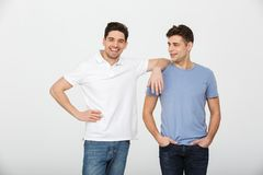 Two handsome men fellas 30s wearing casual t-shirt and jeans smi. Ling and posing together on camera isolated over white background Royalty Free Stock Photography