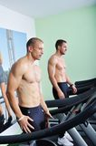 Two handsome men in gym running on the ergometer Royalty Free Stock Photography