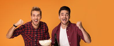 Two handsome men having fun at studio. Best friends having fun at studio. Two men with popcorn posing on orange studio background stock photo