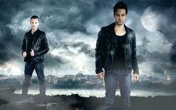 Two handsome men posing in front of the dark city. Two handsome men wearing a black leather jacket in front of the dark city Stock Photography