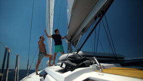 Two handsome men sailing on a luxury yacht. Blue ocean background stock video