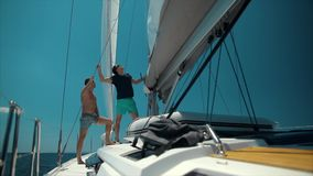 Two handsome men sailing on a luxury yacht. Blue ocean background stock footage