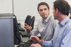 Two handsome men talking while sitting in computer class. Pointing at monitor Stock Photography