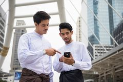 Two Handsome Myanmar businessmen in modern town. Two Handsome Burmese or Myanmar businessmen with longyi traditional dress using smart or mobile phone in Bangkok Stock Photos