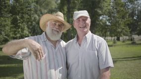 Two handsome old men looking in the camera waving hands in the park. Leisure outdoors. Mature people resting in the. Two positive old men looking in the camera stock video footage