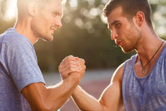 Two handsome strong tense men handshake. Two handsome strong athlete tense men handshake outdoors. Image with lens flare effect Stock Photography