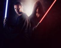 Two handsome warrior holding a light saber. Over a dark background royalty free stock photography