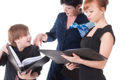 Two handsome women and their boss holding folder with papers. Stock Photos