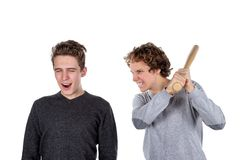 Portrait of two handsome and young furious men fighting with each other on white background stock photo