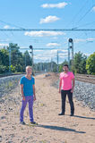 Two handsome young guys jumping. Two handsome young guys standingnear rail track Stock Photo