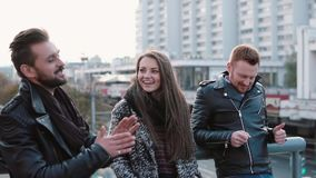 Two handsome young men and a beautiful girl talk and smile standing on the bridge in the city. Steadicam shot, slow mo. Two handsome young men and a beautiful stock footage