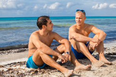 Two handsome young men chatting on a beach. In their swimsuits sitting side by side on the sand with their backs to the ocean enjoying a relaxing summer day at royalty free stock photos