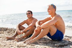 Two handsome young men chatting on a beach Royalty Free Stock Image