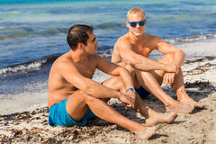 Two handsome young men chatting on a beach. In their swimsuits sitting side by side on the sand with their backs to the ocean enjoying a relaxing summer day at stock image