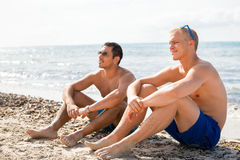 Two handsome young men chatting on a beach. In their swimsuits sitting side by side on the sand with their backs to the ocean enjoying a relaxing summer day at royalty free stock images