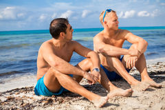 Two handsome young men chatting on a beach. In their swimsuits sitting side by side on the sand with their backs to the ocean enjoying a relaxing summer day at stock images