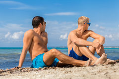 Two handsome young men chatting on a beach Royalty Free Stock Images