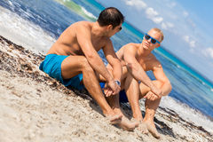 Two handsome young men chatting on a beach. In their swimsuits sitting side by side on the sand with their backs to the ocean enjoying a relaxing summer day at stock photos