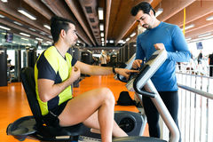 Two handsome young men doing cardio training in gym. Royalty Free Stock Photo