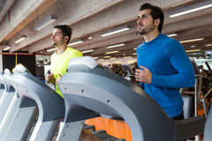 Two handsome young men doing cardio training in gym. Stock Photos