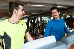 Two handsome young men doing cardio training in gym. Royalty Free Stock Photos