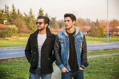 Two handsome young men, friends, in a park Stock Photo