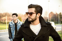 Two handsome young men, friends, in a park. Two handsome casual trendy young men, 2 friends, in an urban park walking and chatting together Stock Photo