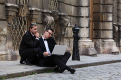 Two handsome young men with a laptop on the street Stock Image