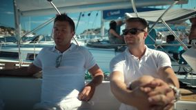 Two handsome young men listening friend on the yacht. Luxury stock video footage