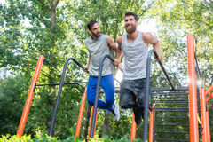 Two handsome young men passionate about fitness doing dips exerc Stock Photography